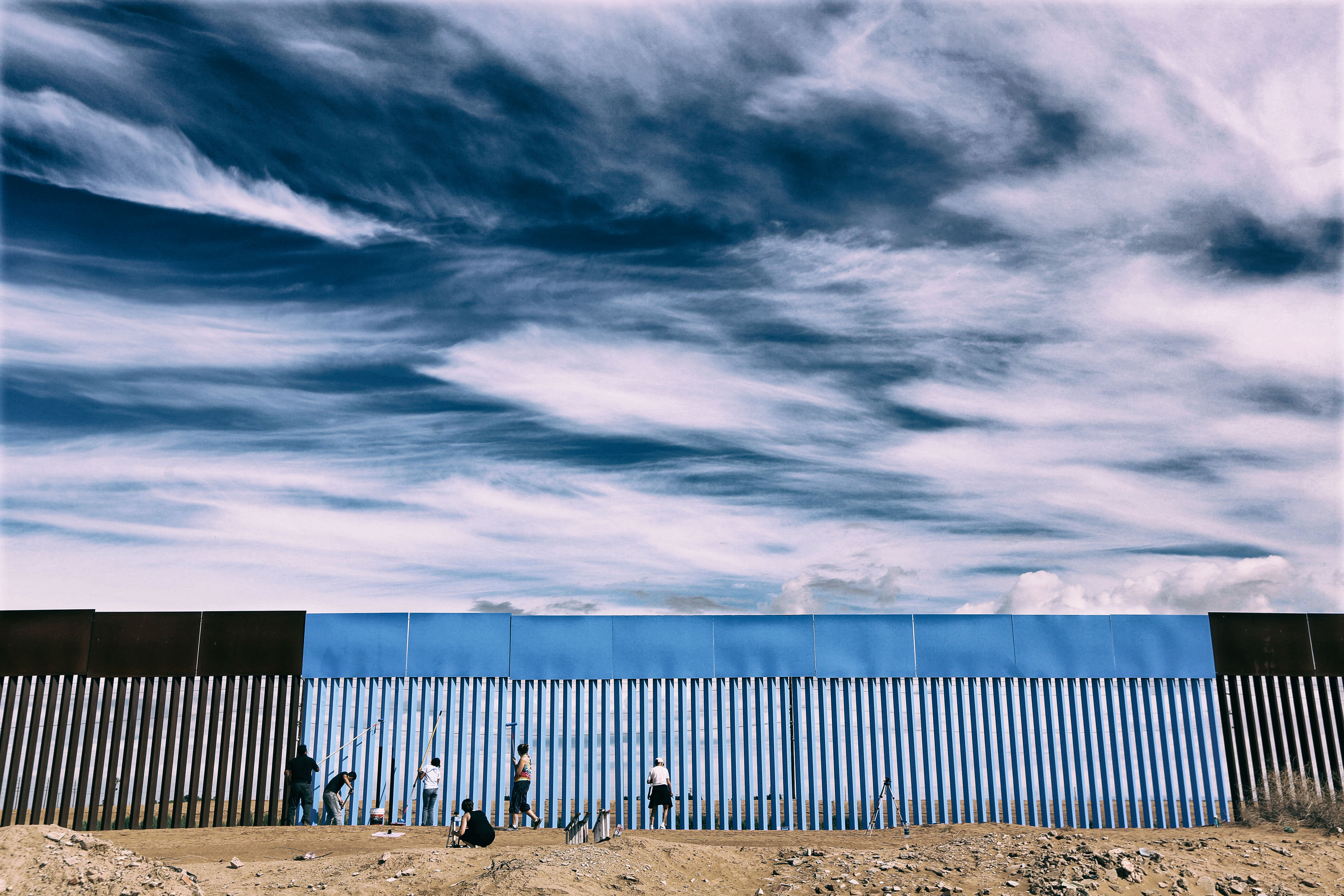 "Volunteers paint the border fence between the U.S. and Mexico to give it the illusion of transparency during her ""Borrando la Frontera"" Art Project in Mexicali, Mexico. Photo: Sandy Huffaker"