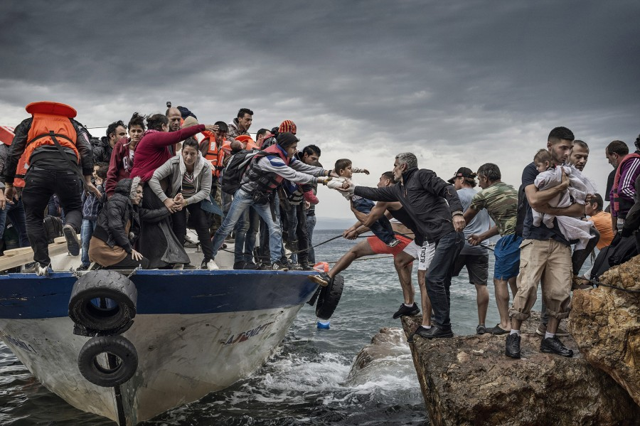 Refugees and Migrants aboard fishing boat driven by smugglers reach the coast of the Greek Island of Lesbos after crossing the Aegean sea from Turkey on October 11, 2015. The number of people arriving here has surged in October to what officials attribute efforts to make the trip before the weather turns cold in winter. According to the island's Ministry of Interior, nearly 30,000 people landed here during the first week of October alone, adding to the 160,000 who arrived in September. Most of the new arrivals are from Syria, with large contingents from Afghanistan, Iraq, Eritrea and North African nations. European governments are under pressure to help genuine refugees while limiting the number of economic migrants entering the European Union.